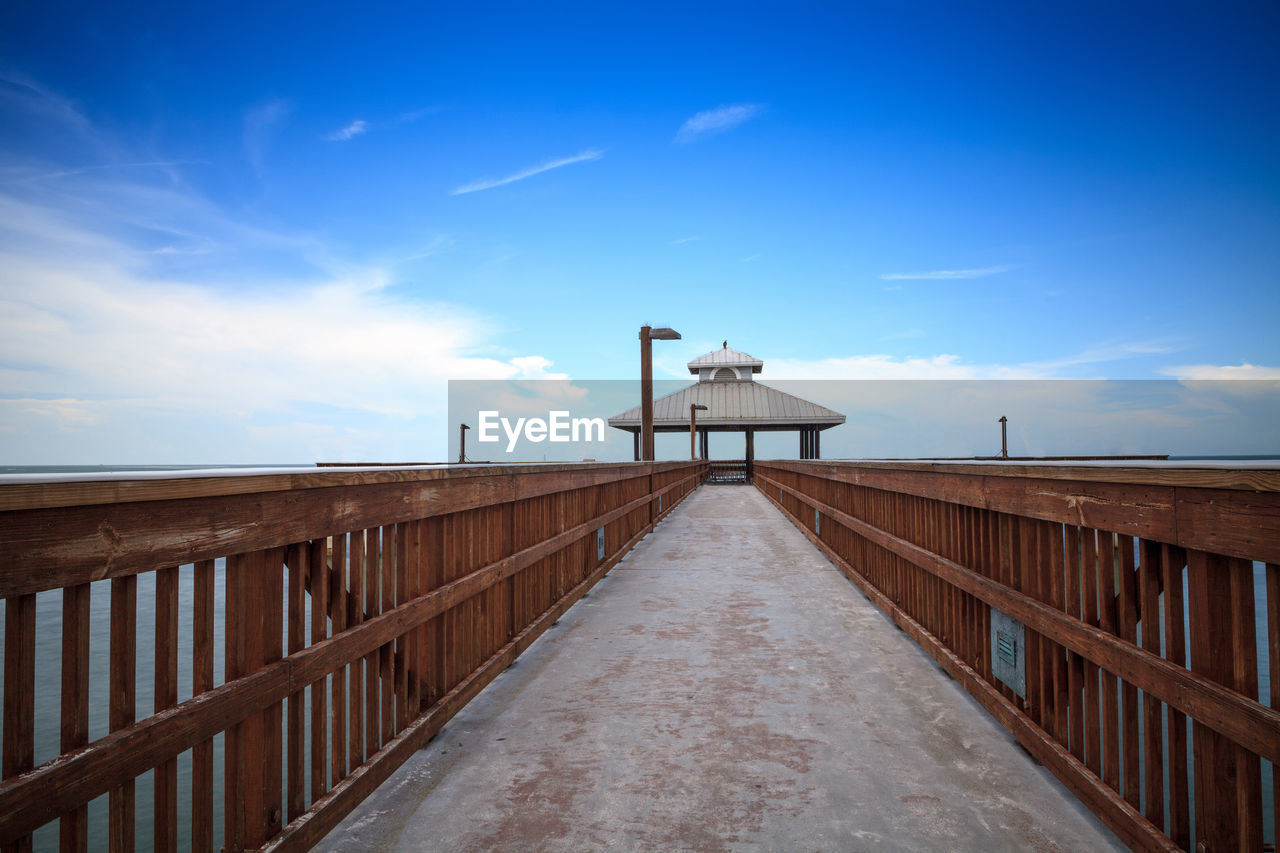 sky, built structure, architecture, railing, direction, cloud - sky, the way forward, nature, blue, no people, day, diminishing perspective, building exterior, outdoors, wood - material, footpath, protection, lighting equipment, security, low angle view