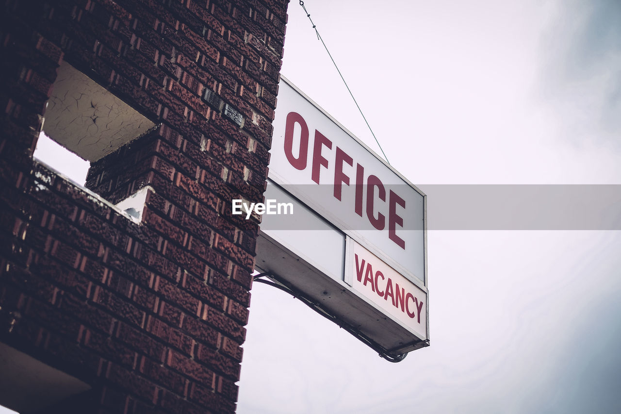 Low Angle View Of Office Vacancy Sign On Brick Wall Against Sky