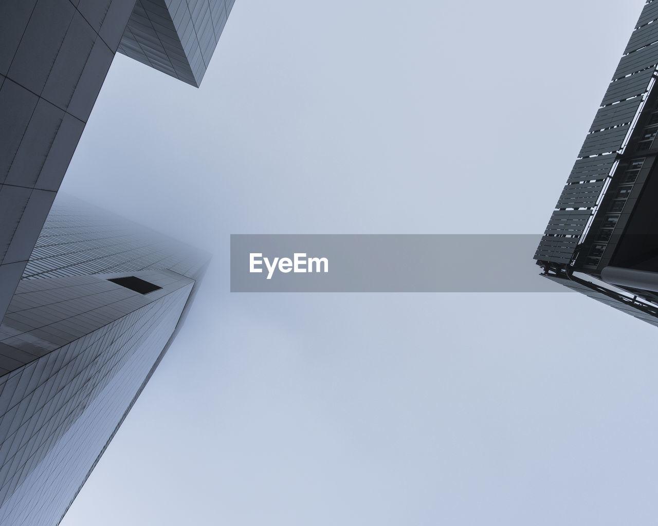 Directly Below Shot Of Modern Buildings Against Clear Sky