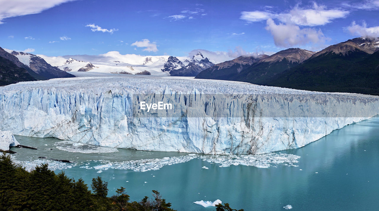 Ice bergs in sea against mountains during winter