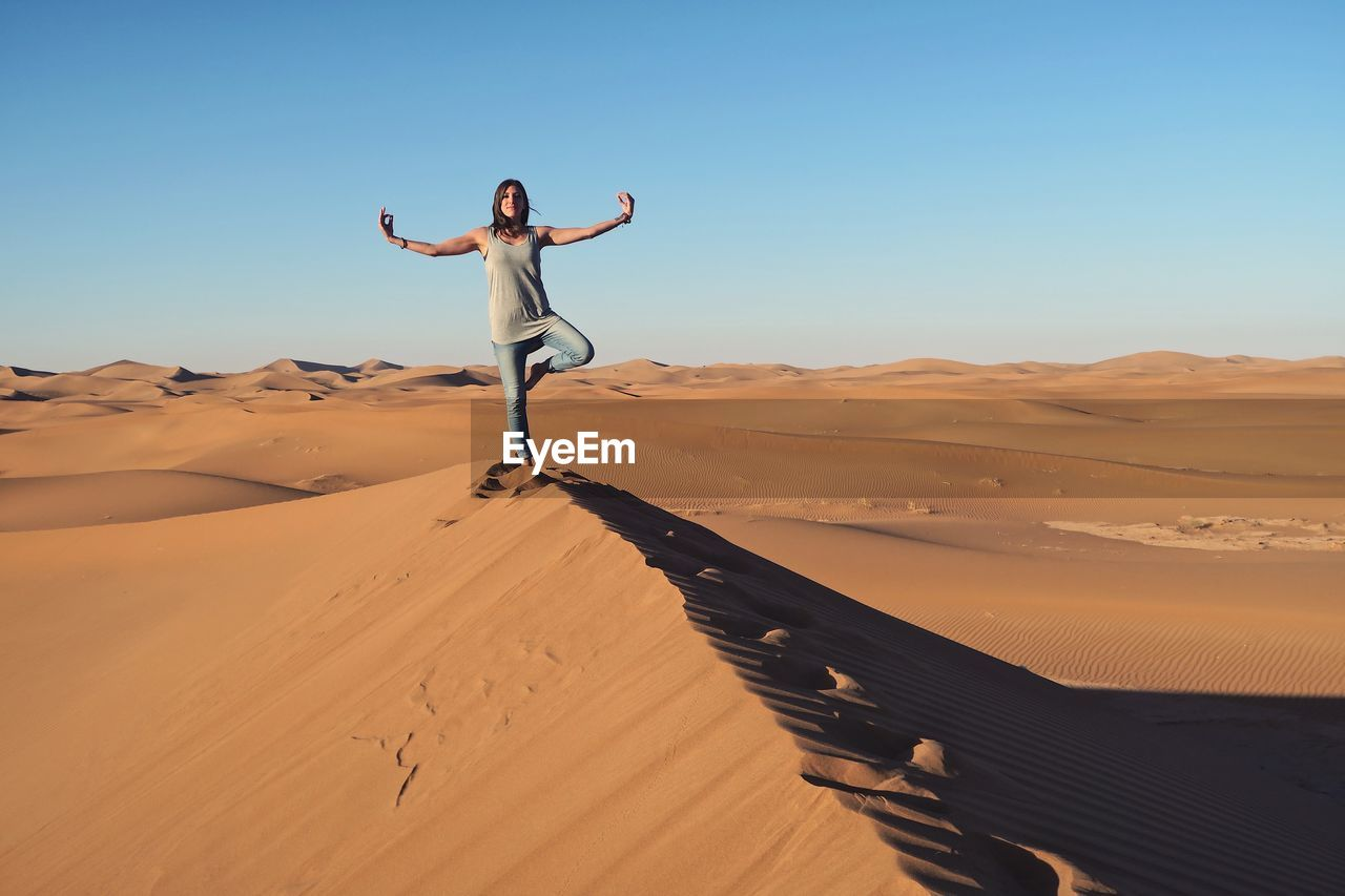 Woman practicing yoga on sand dune at desert against clear blue sky
