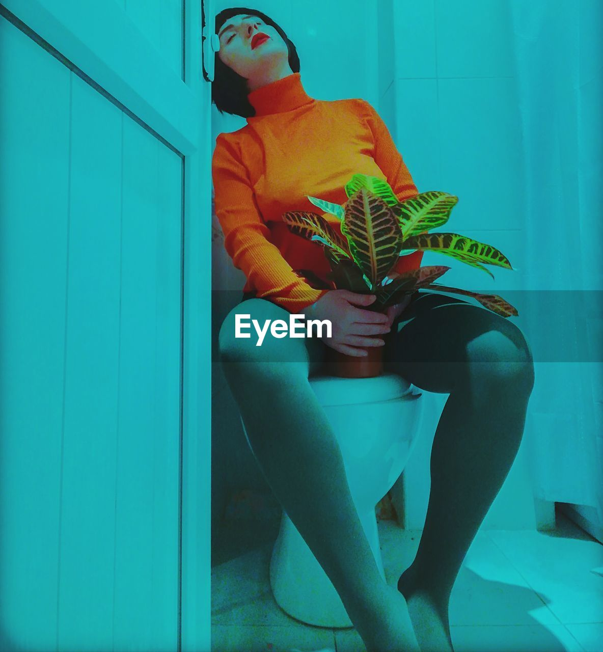 Young woman with potted plant sitting on toilet bowl in bathroom