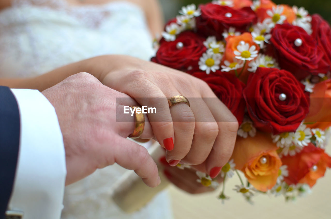 wedding, bride, love, human hand, togetherness, flower, celebration, real people, wedding ceremony, celebration event, life events, women, bridegroom, groom, bouquet, men, ceremony, human body part, religion, red, holding, two people, bonding, couple - relationship, married, wife, indoors, lifestyles, close-up, wedding dress, food, freshness, day, adult, people