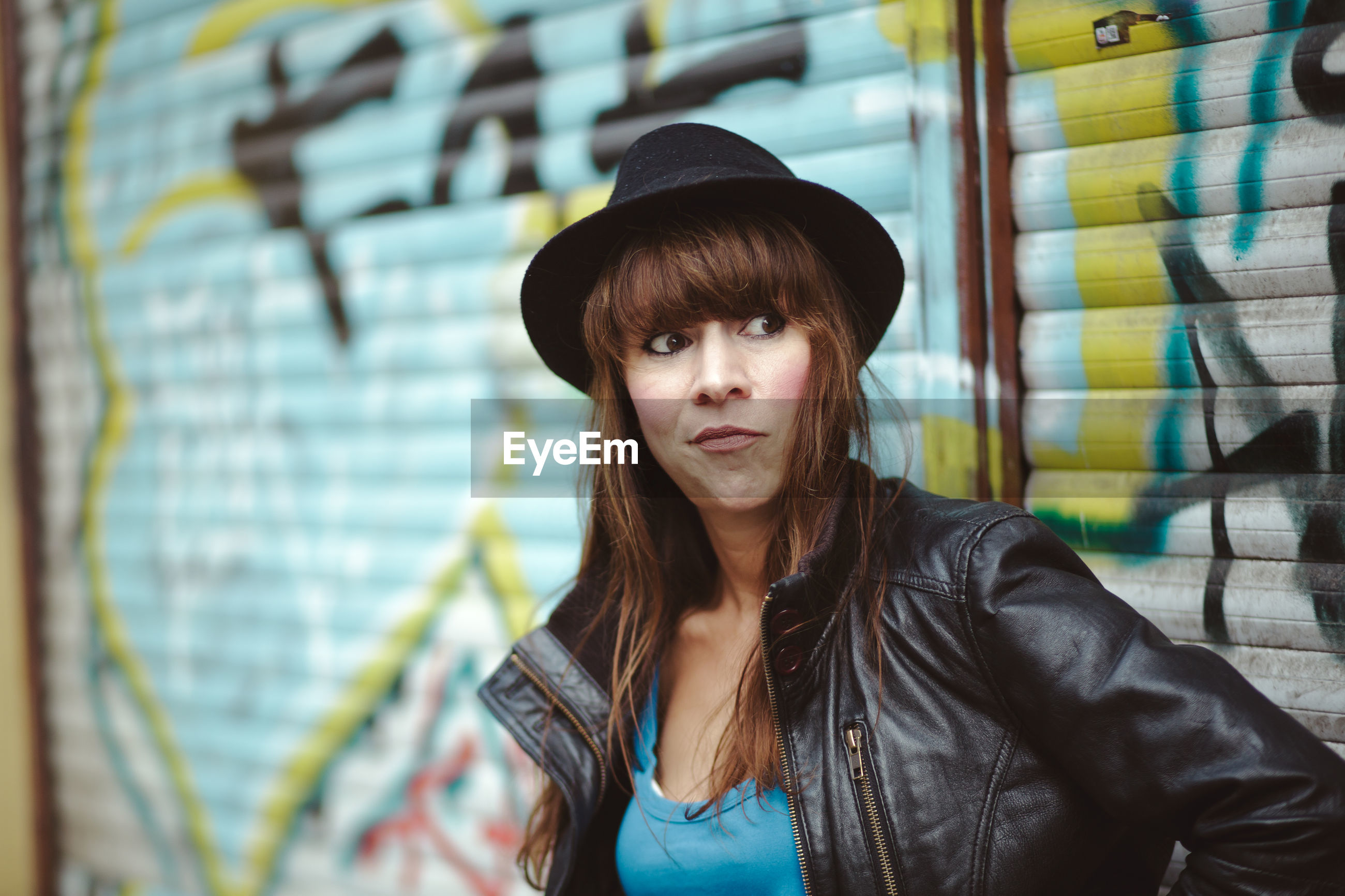 Woman wearing hat against graffiti shutter in city