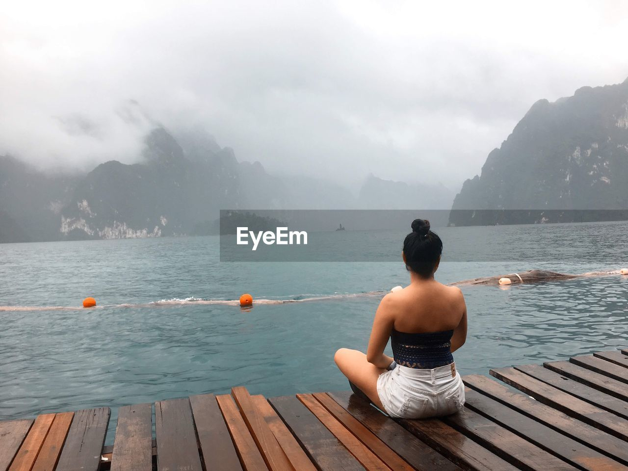 Rear view of woman sitting on pier over sea against mountains