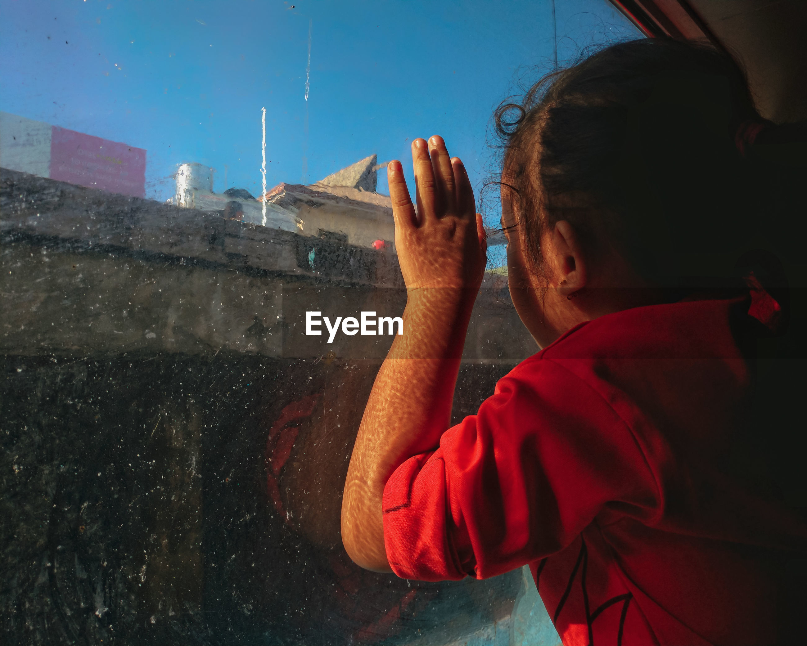 Girl looking through window while sitting in boat