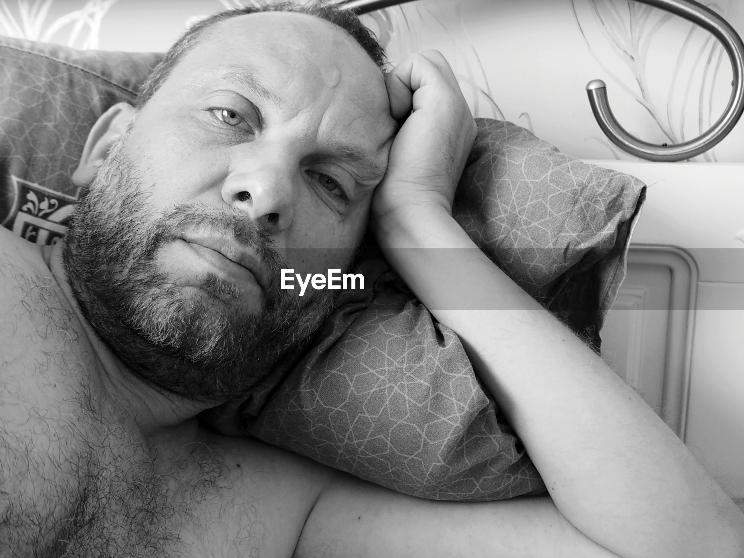 Portrait of shirtless man lying on bed at home