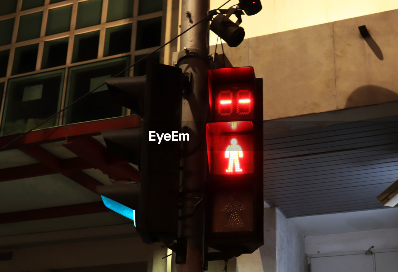 architecture, low angle view, road signal, built structure, stoplight, sign, safety, no people, building exterior, communication, red, light, red light, illuminated, lighting equipment, guidance, human representation, city, focus on foreground, outdoors