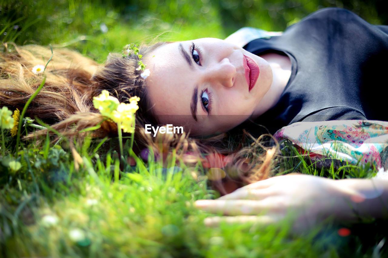 Portrait of woman lying on grassy field