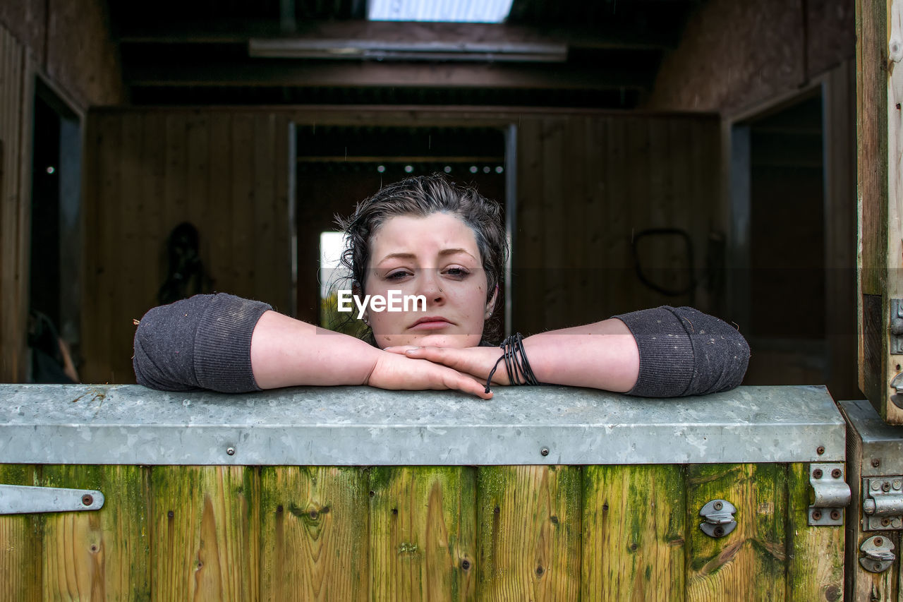Portrait Of Woman Leaning On Wooden Gate In Stable
