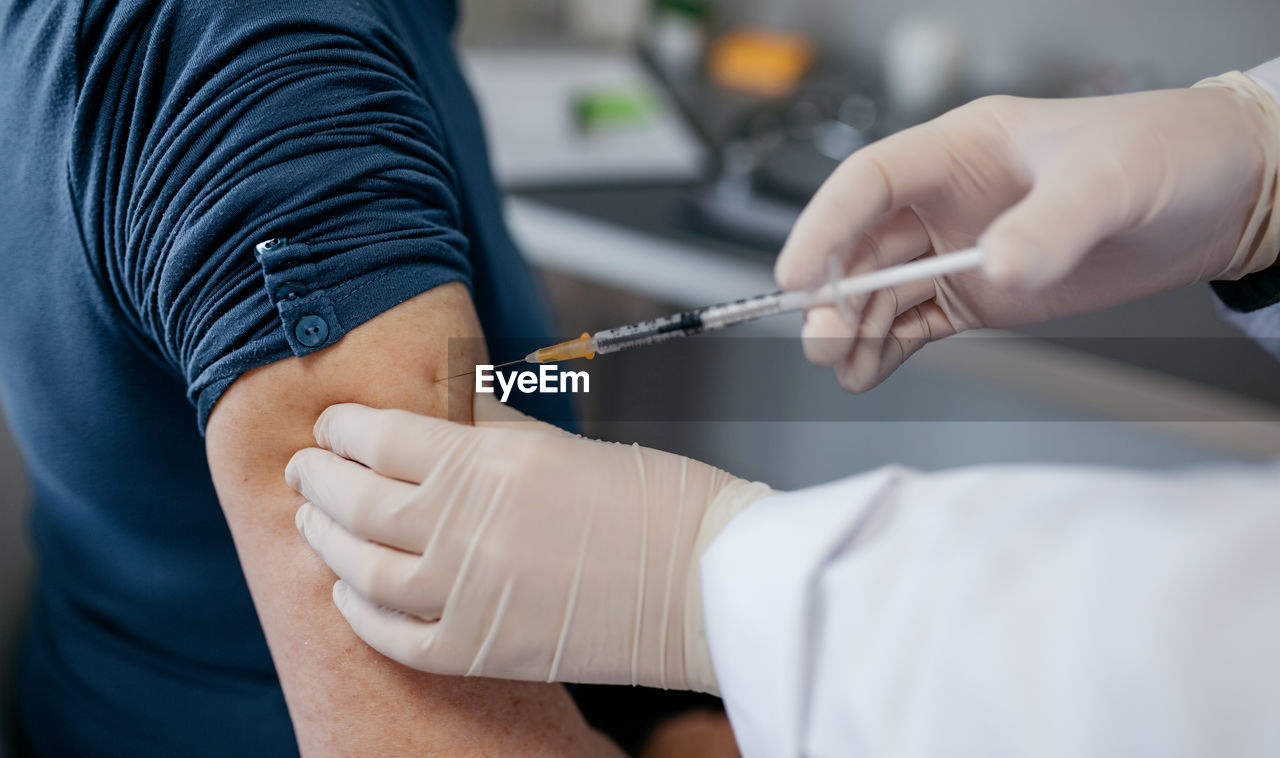 Cropped hand of doctor injecting syringe in patients arm