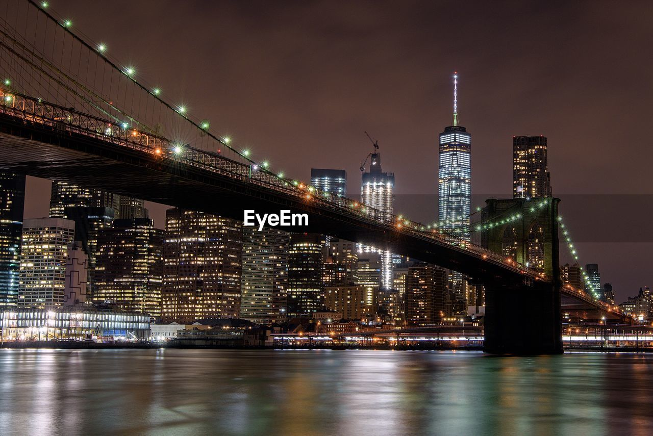 Brooklyn Bridge Over East River By One World Trade Center In Illuminated City At Night