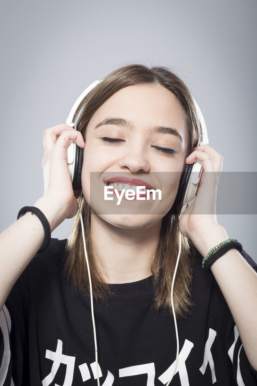 Close-up of young woman listening music on headphones against gray background