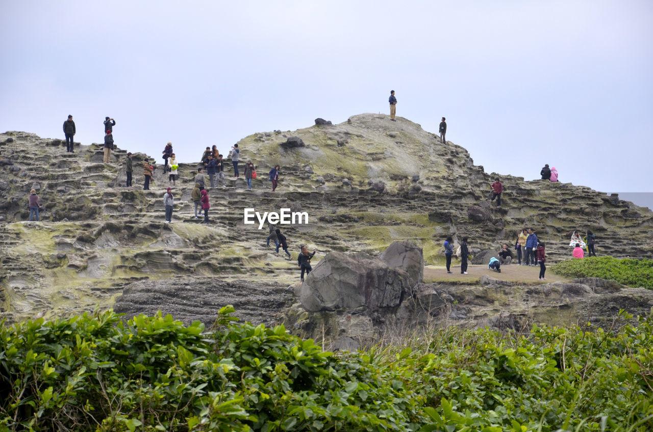 Group of people walking on rocky landscape