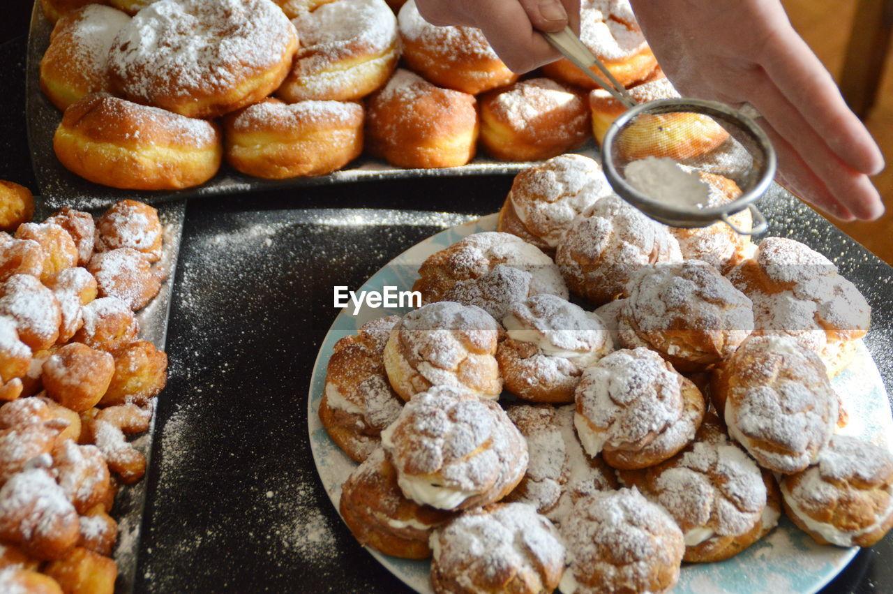 Close-Up Of Hand Powdering Donuts