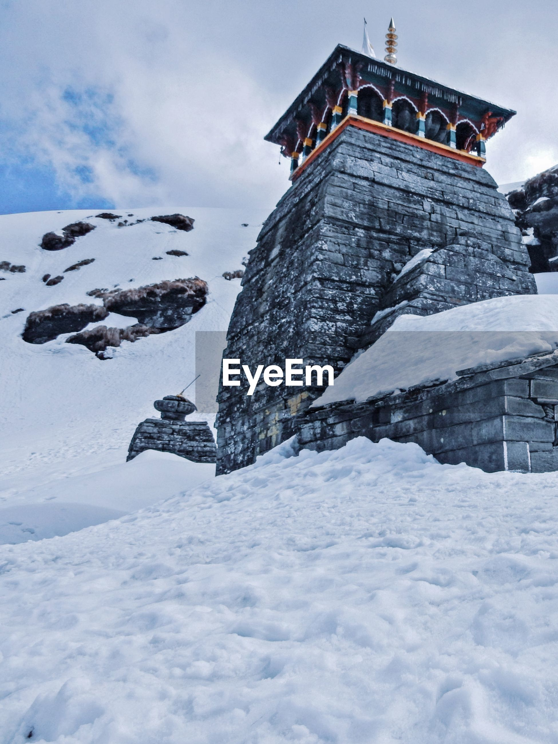 Low angle view of tunganath temple covered with snow  against sky