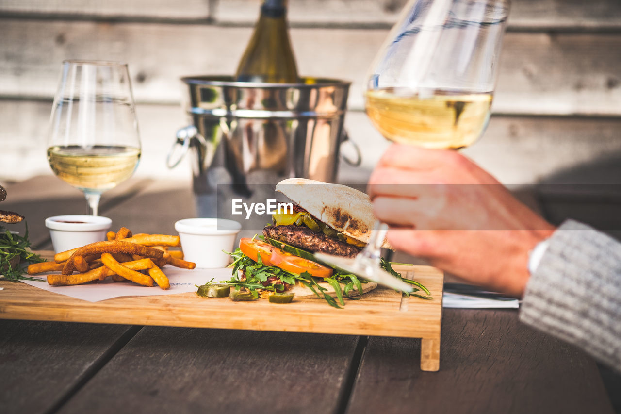 food and drink, drink, refreshment, food, table, wine, freshness, glass, alcohol, wineglass, ready-to-eat, human hand, sandwich, real people, unhealthy eating, serving size, fast food, one person, indoors, wood - material, hand, tray, hamburger, snack