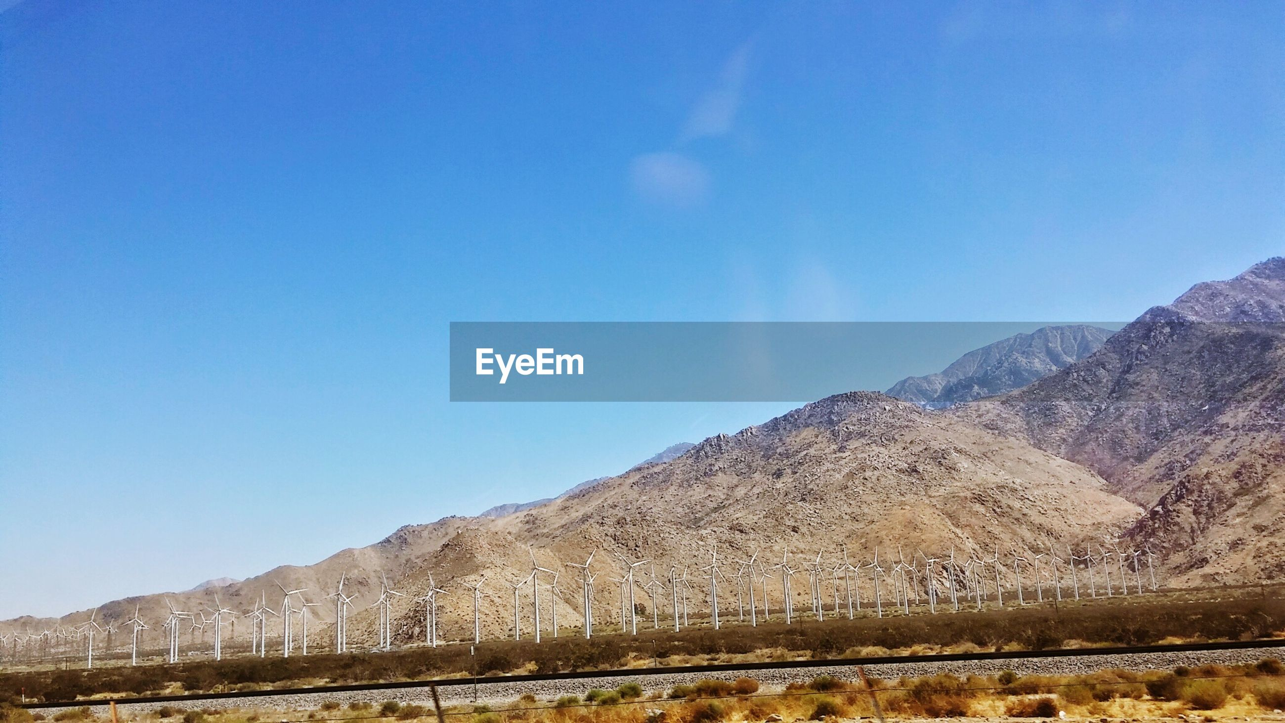 Low angle view of windmills against mountains