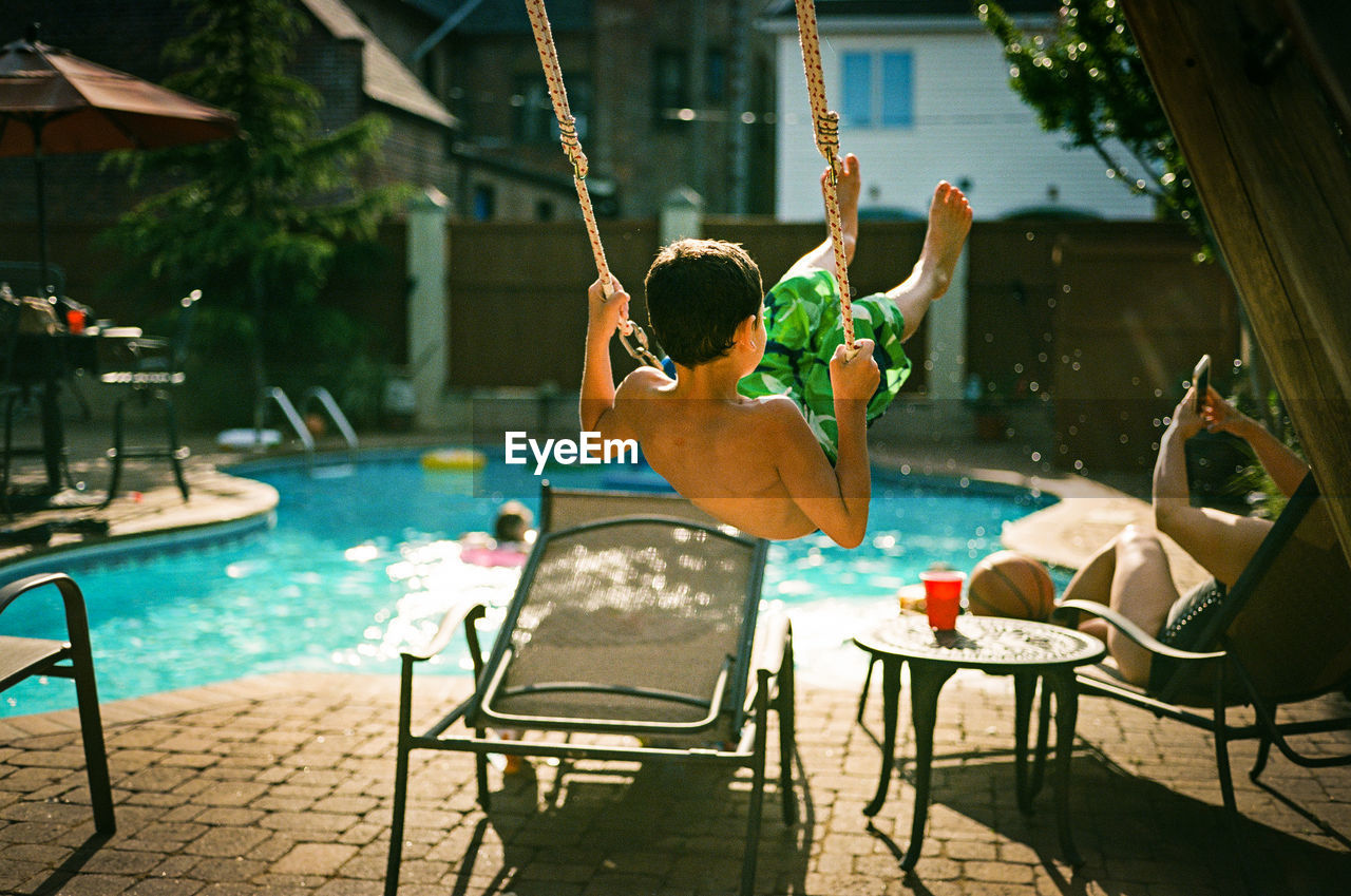 Rear View Of Boy Playing On Swing At Poolside
