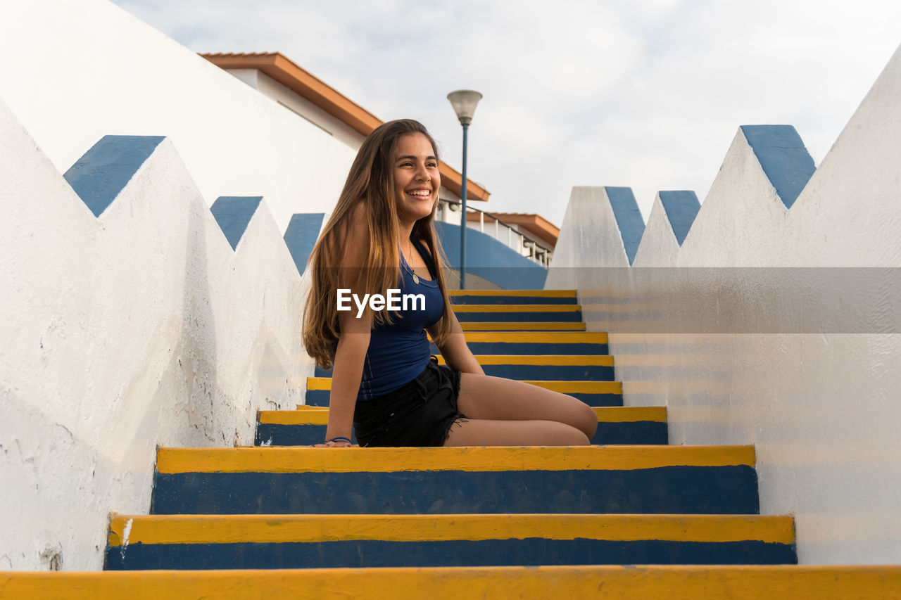Smiling young woman sitting on staircase against sky