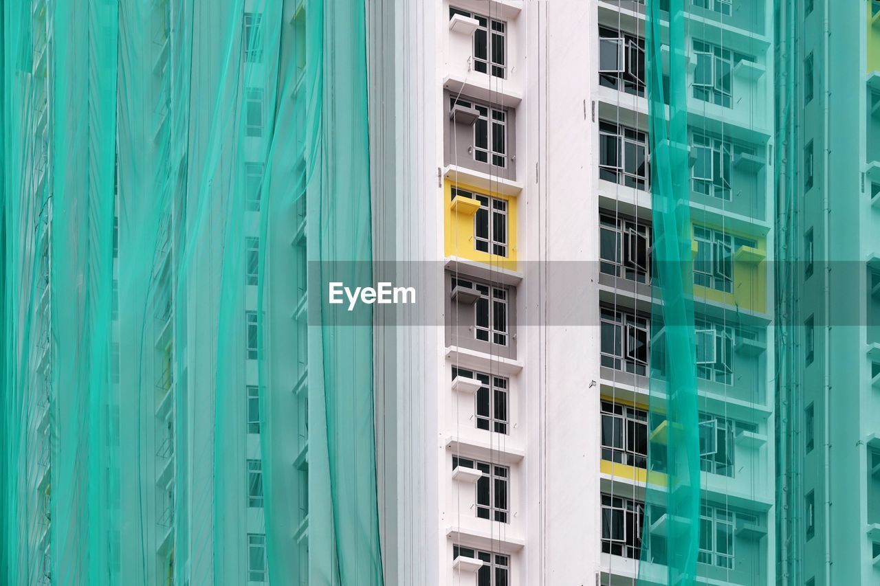 built structure, architecture, building exterior, window, green color, building, no people, residential district, day, close-up, yellow, outdoors, glass - material, high angle view, in a row, full frame, office, city, industry, sunlight, apartment, turquoise colored
