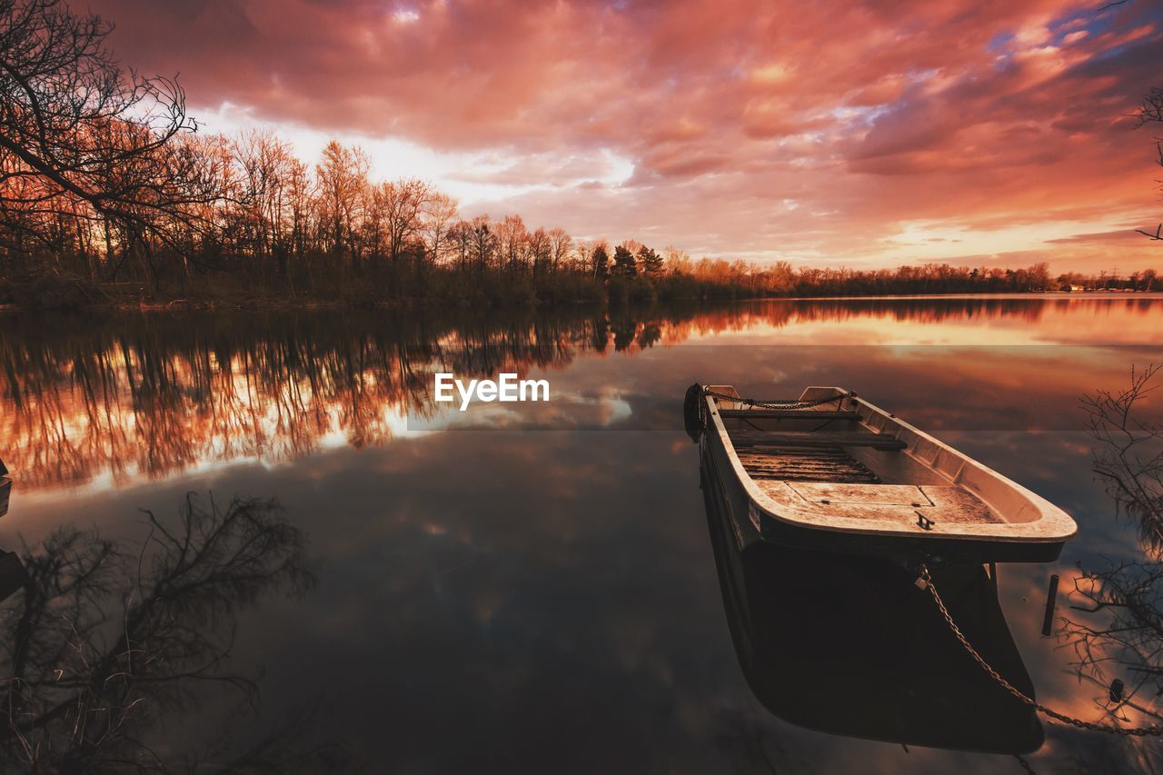 Boat moored with chain in lake against cloudy sky