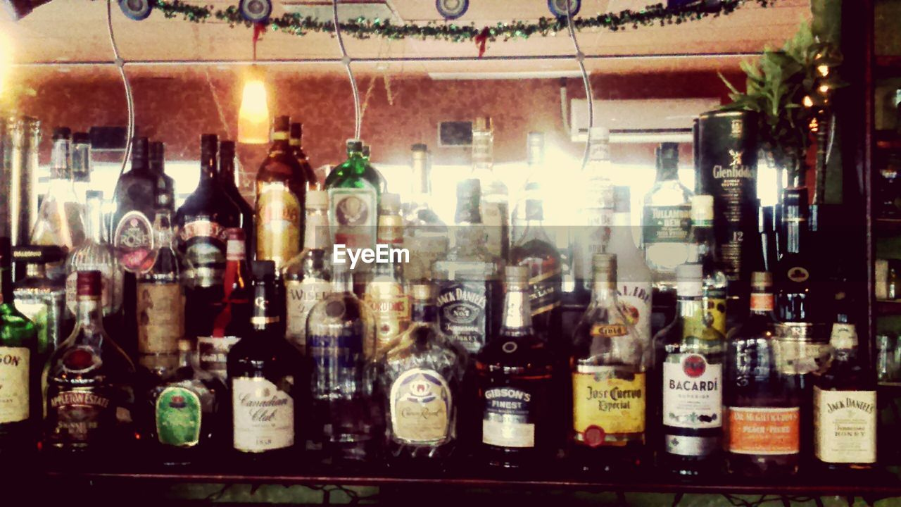 bottle, indoors, alcohol, food and drink, refreshment, in a row, drink, retail, shelf, no people, large group of objects, variation, arrangement, bar - drink establishment, choice, illuminated, store, close-up, night