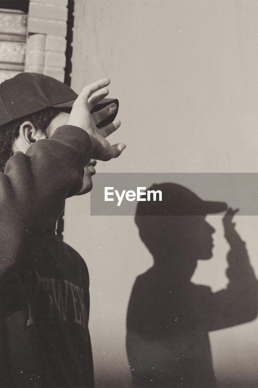 Shadow of man shielding eyes on wall