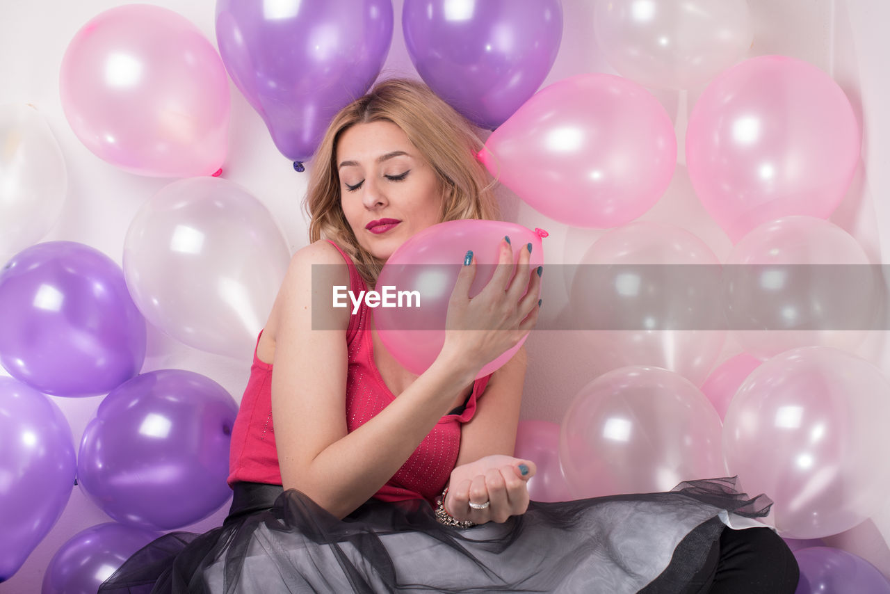 Beautiful young woman with closed eyes sitting amidst balloons