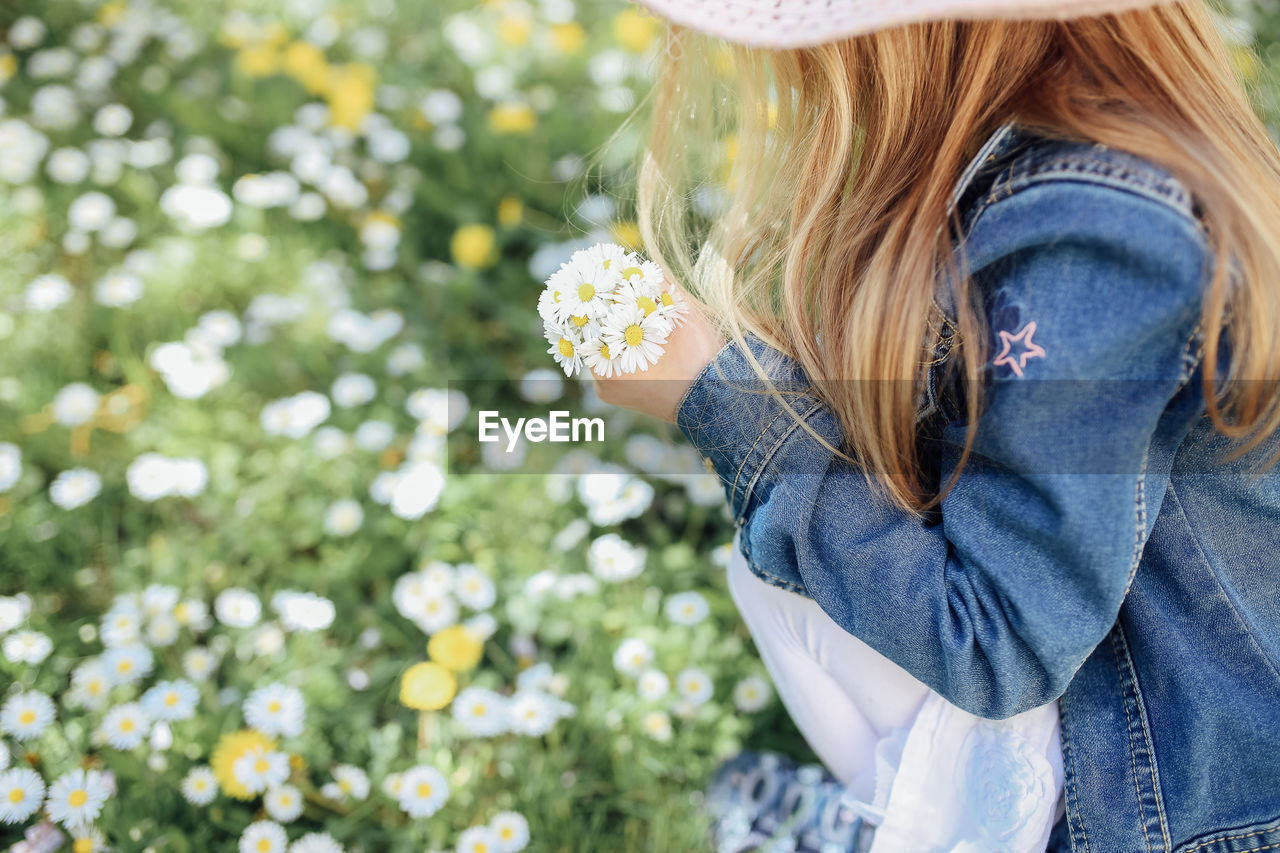 plant, one person, blond hair, flowering plant, flower, hair, casual clothing, day, long hair, women, leisure activity, nature, child, hairstyle, holding, focus on foreground, lifestyles, freshness, outdoors, jeans