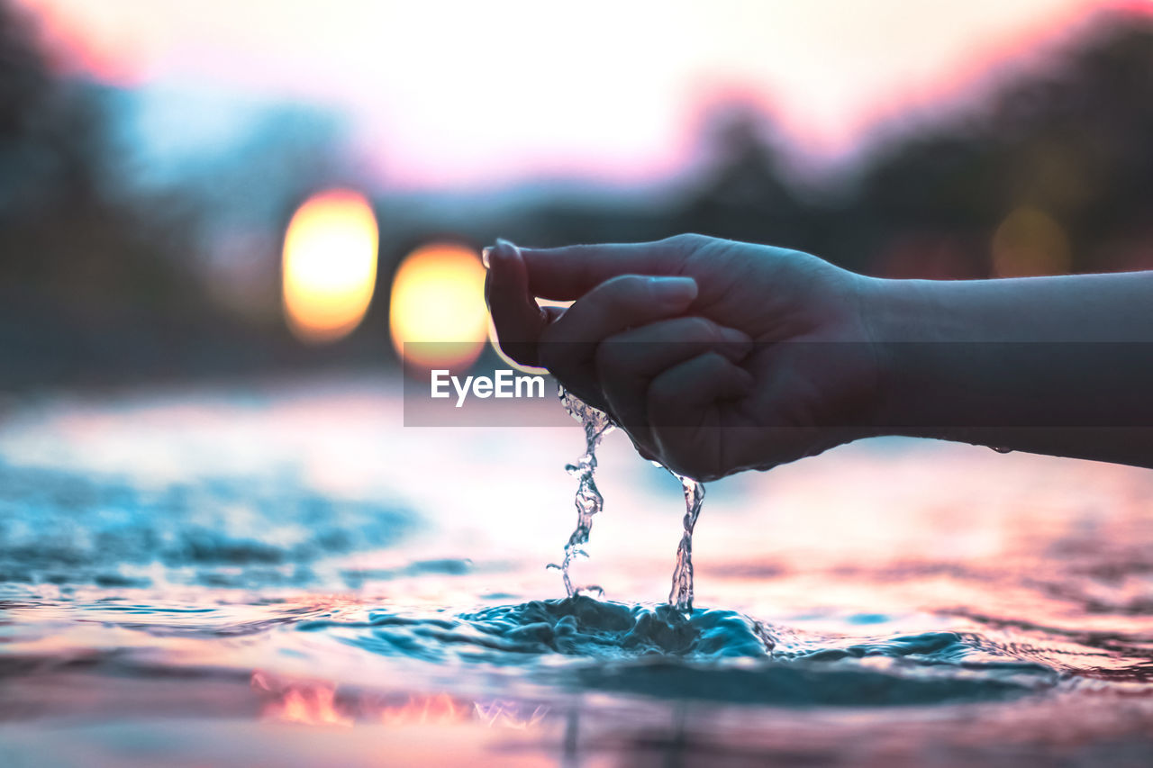 Cropped hand of woman touching water in lake during sunset