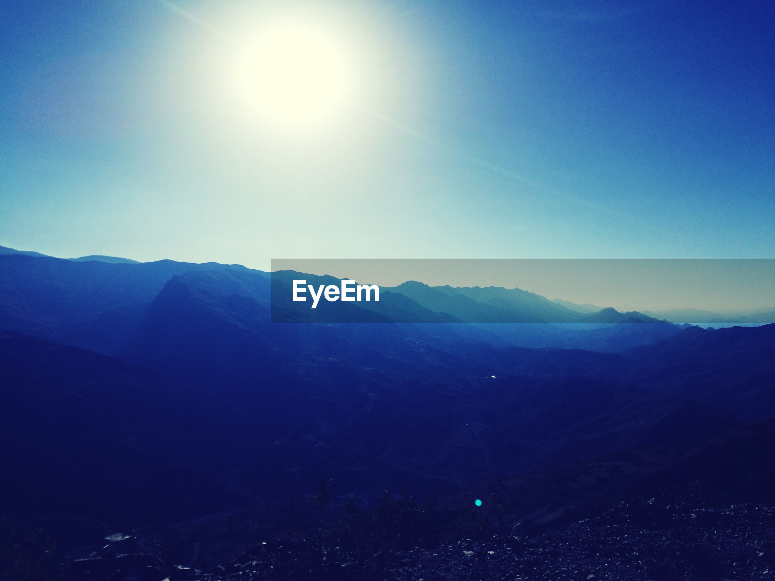 mountain, scenics, beauty in nature, blue, nature, tranquil scene, tranquility, sunlight, mountain range, sky, clear sky, outdoors, idyllic, sun, no people, low angle view, silhouette, landscape, day, tree