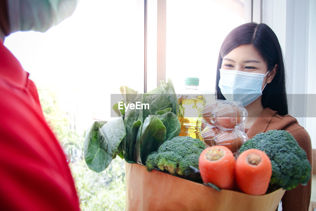 Smiling woman wearing mask taking delivery of vegetables at home