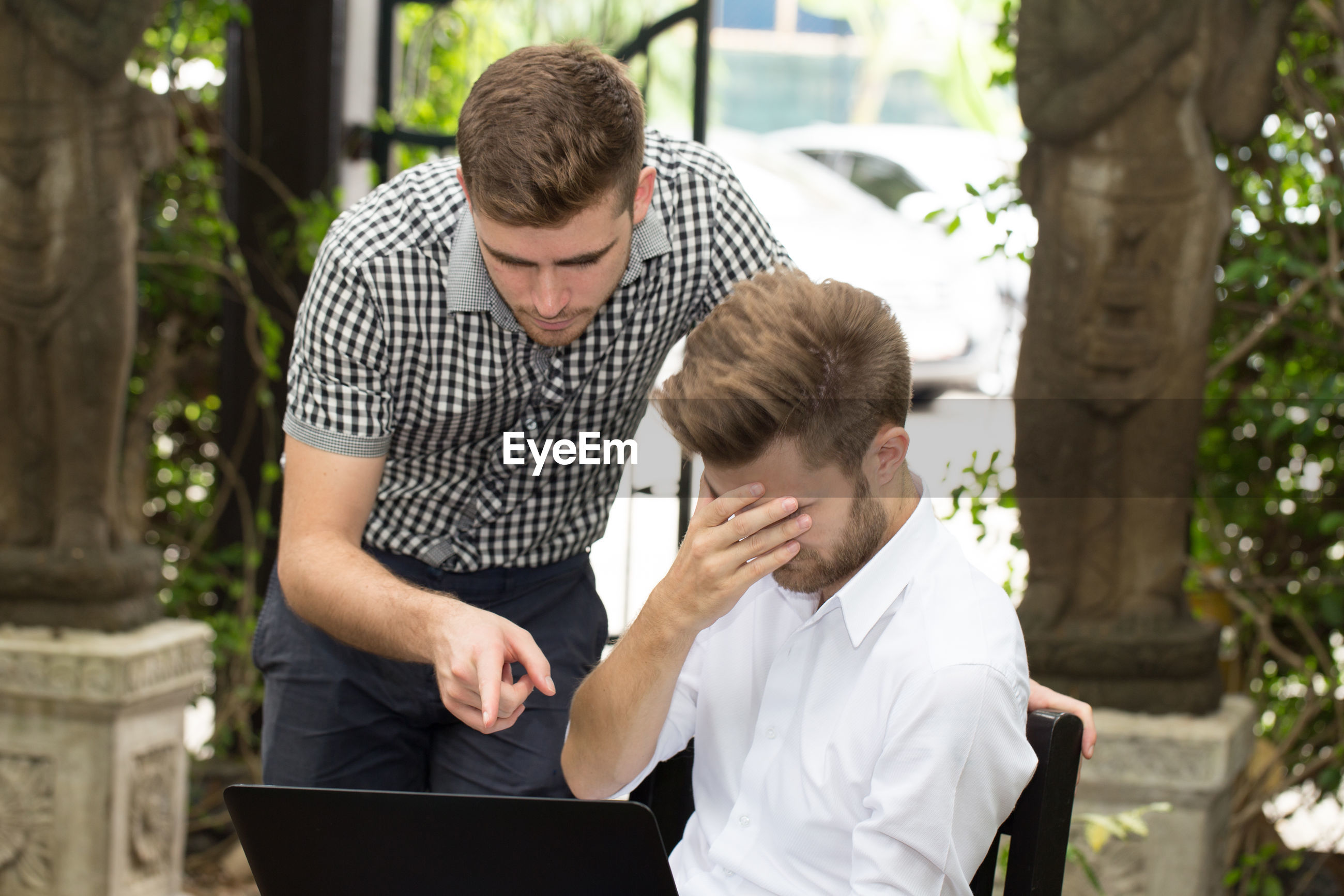 Man pointing at laptop while standing by stressed friend