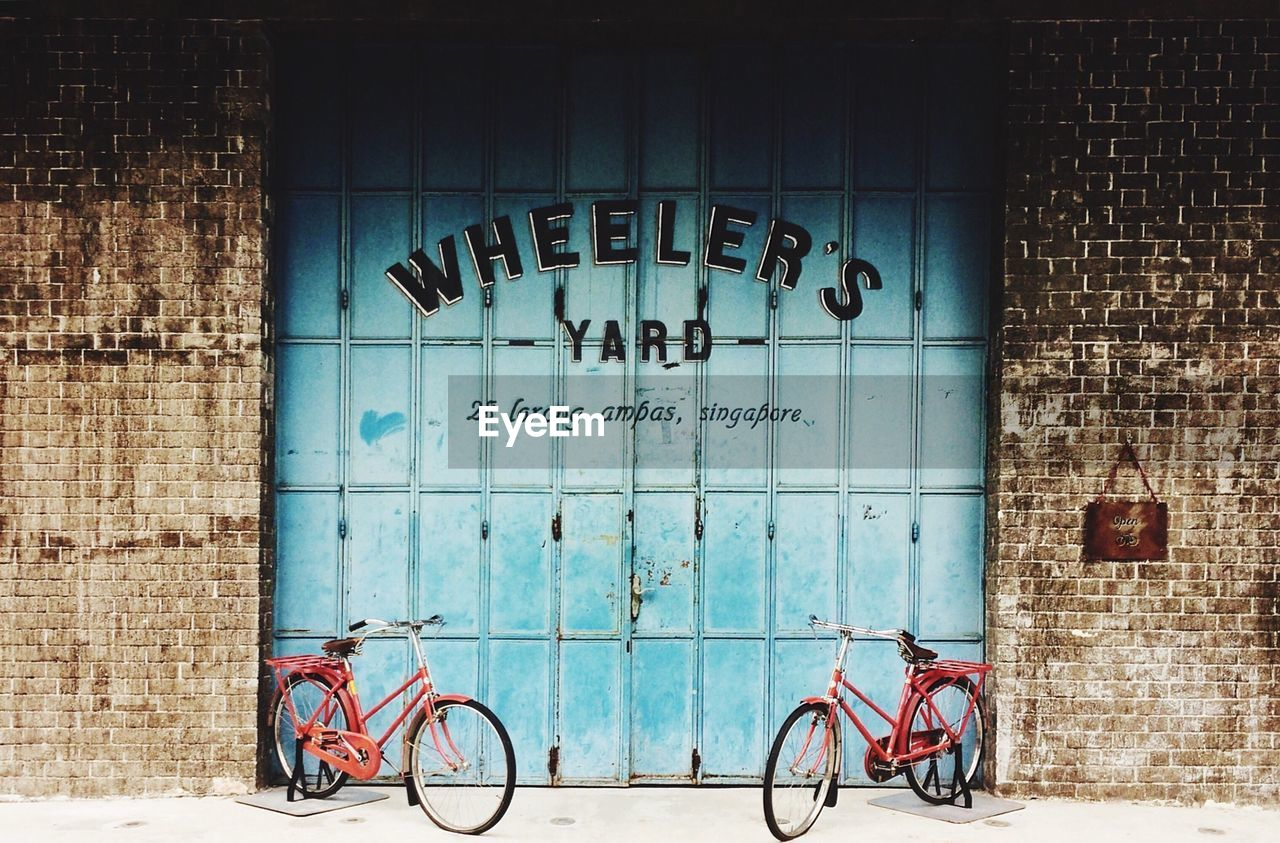 bicycle, text, architecture, built structure, transportation, day, mode of transport, building exterior, communication, stationary, land vehicle, no people, outdoors, blue, bicycle rack