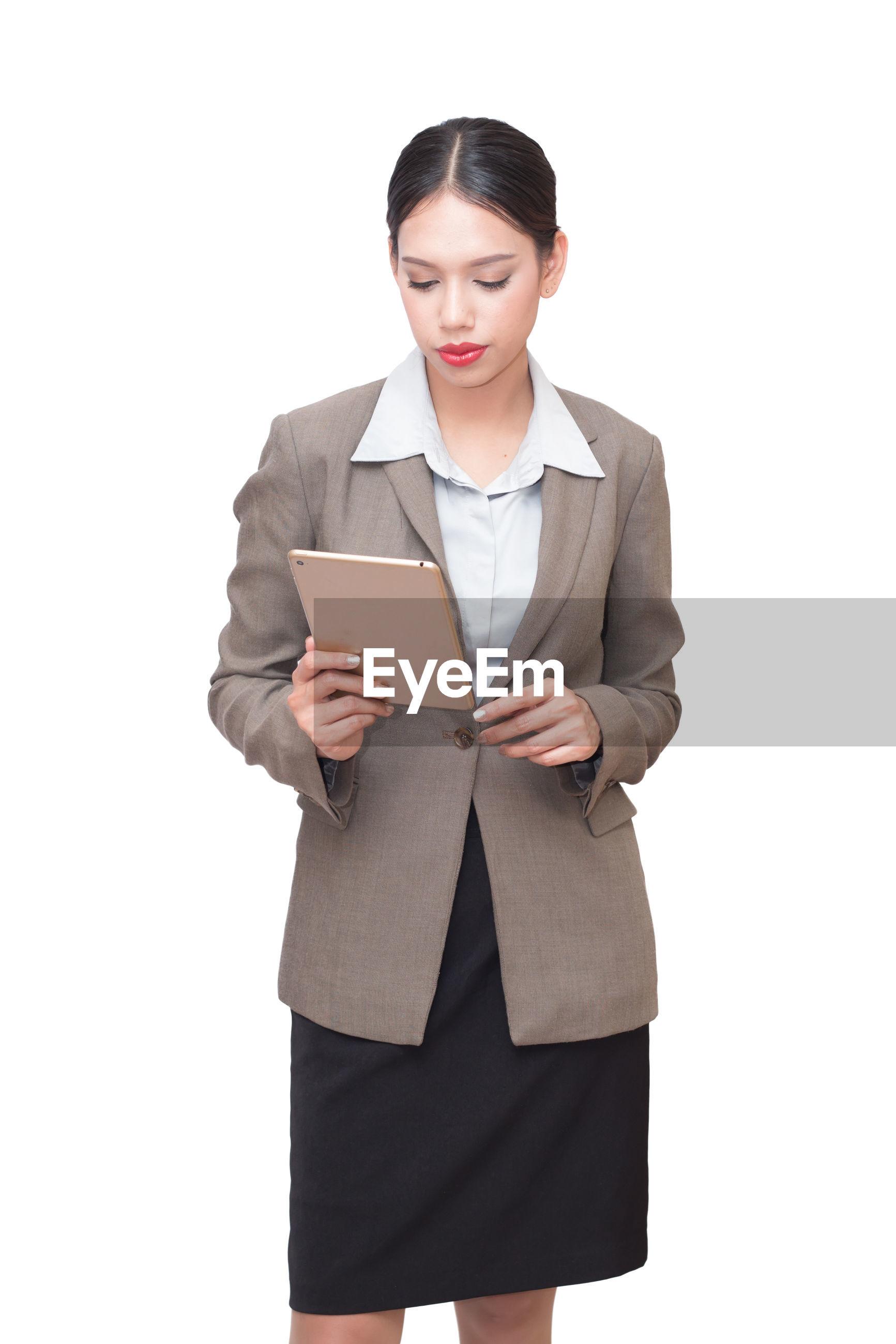 Businesswoman using digital tablet against white background