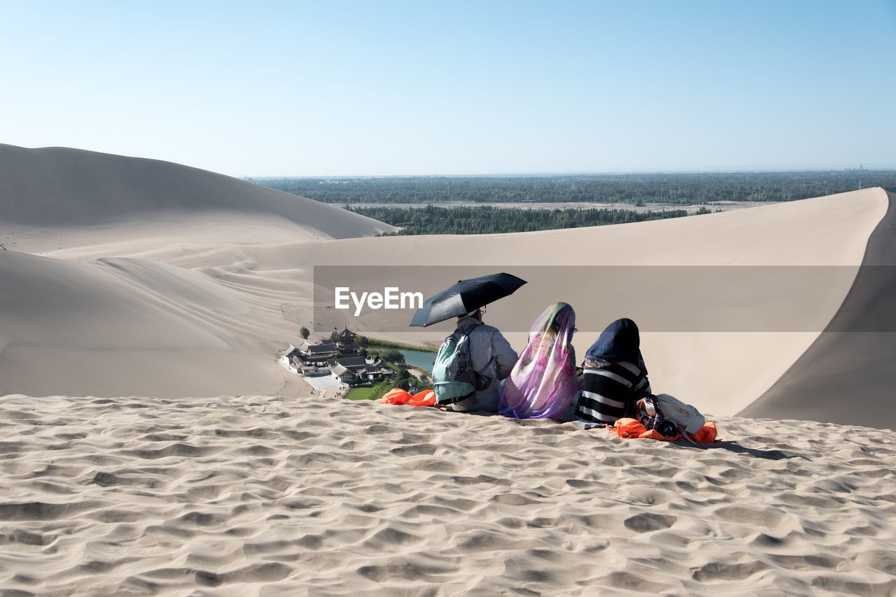 sand, real people, leisure activity, nature, beach, day, scenics, lifestyles, outdoors, clear sky, two people, beauty in nature, men, vacations, sand dune, motion, arid climate, weekend activities, togetherness, sky, adventure, low section, women, people