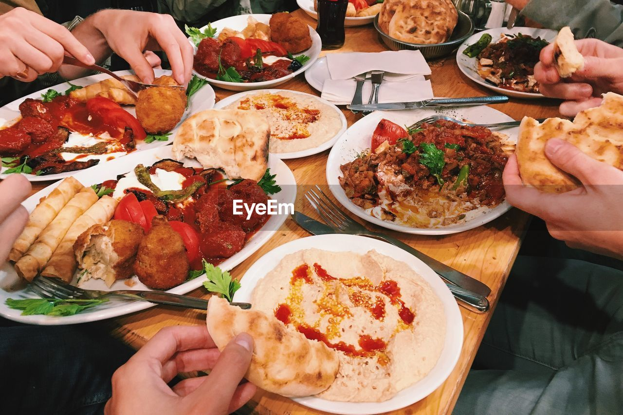 High Angle View Of Friends Eating Lunch At Restaurant