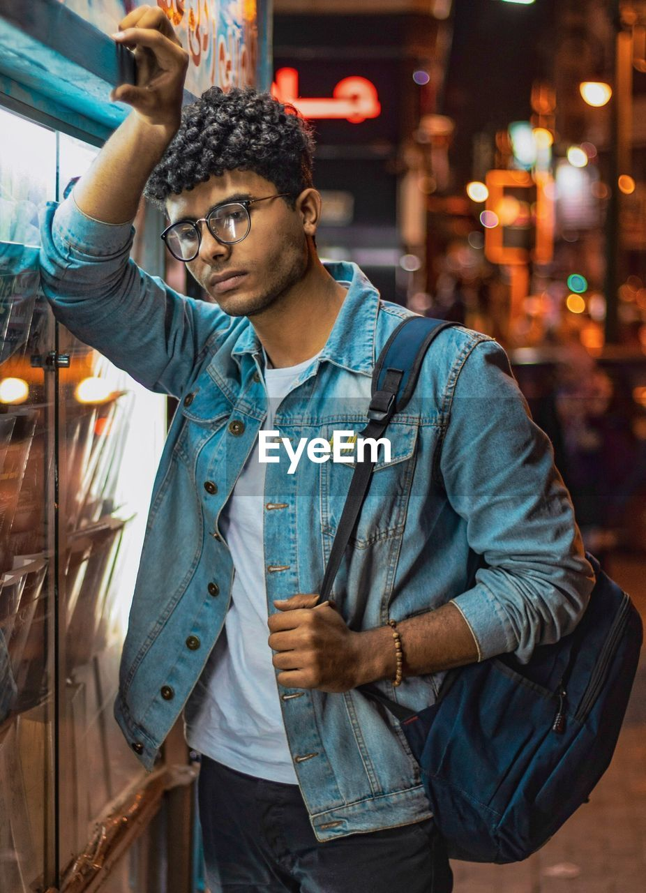 young men, one person, young adult, casual clothing, three quarter length, standing, night, real people, front view, leisure activity, lifestyles, waist up, looking away, men, illuminated, focus on foreground, looking, architecture, jacket, outdoors