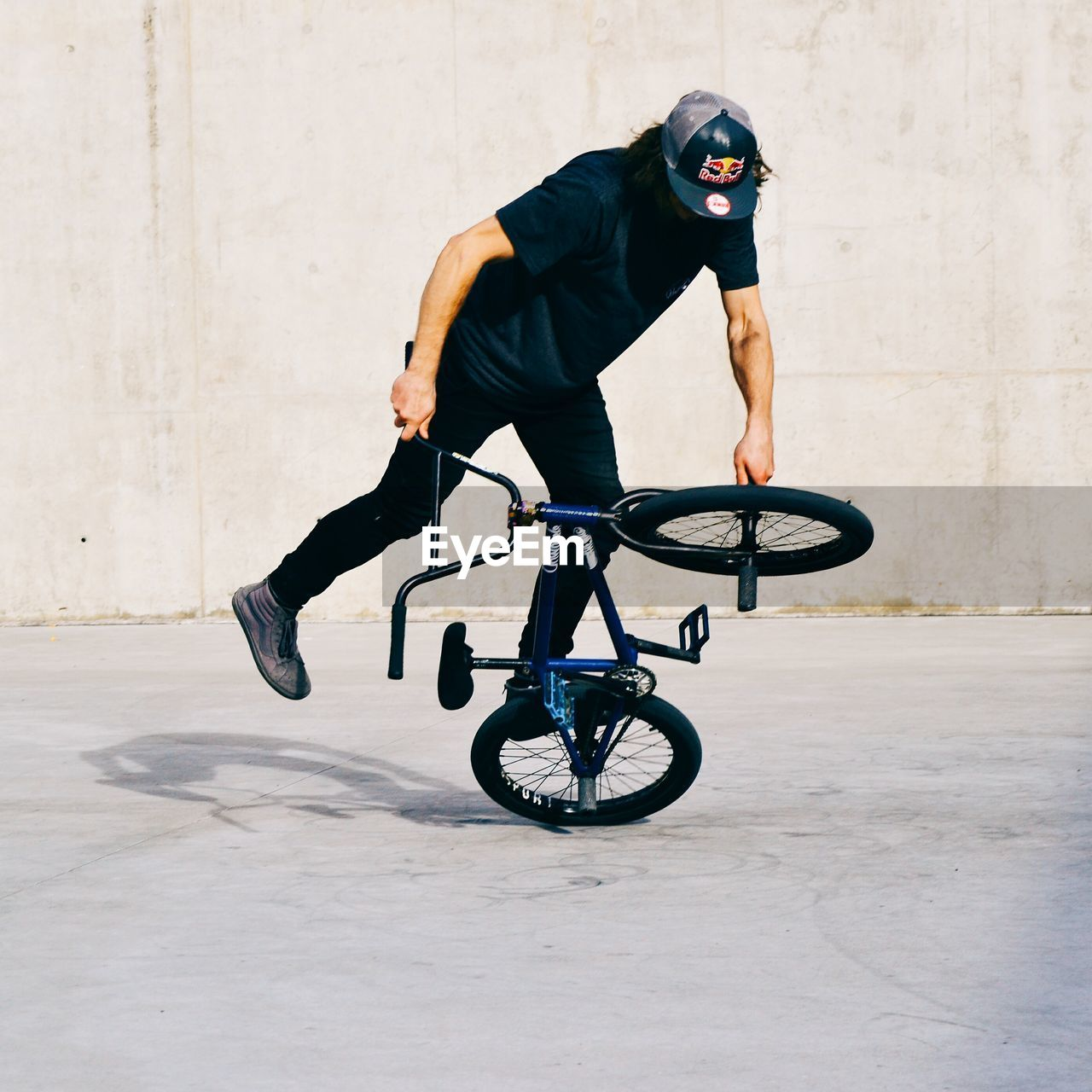 FULL LENGTH OF MAN RIDING BICYCLE ON WALL