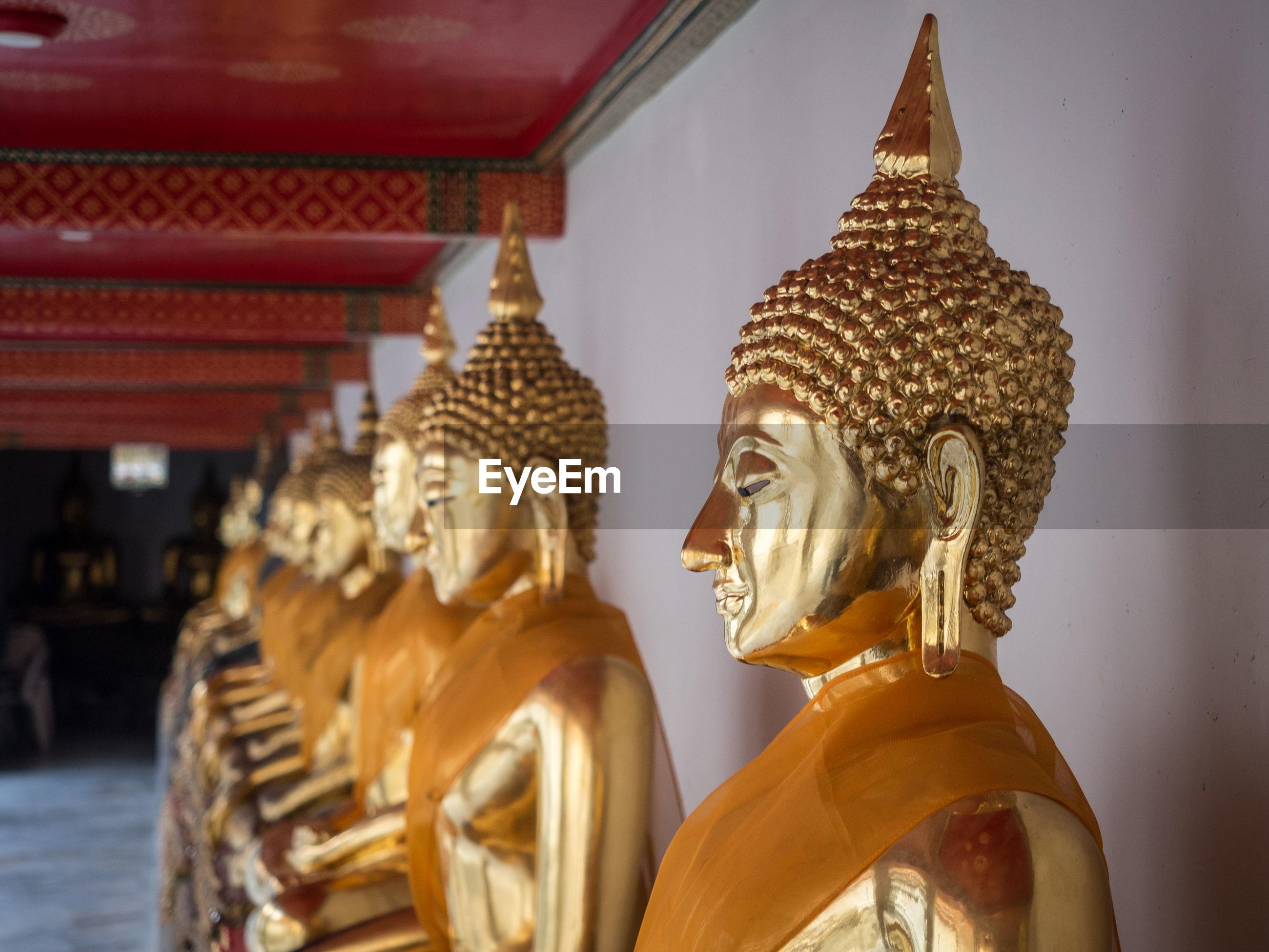 Row of golden buddha statues at wat pho temple, bangkok, thailand
