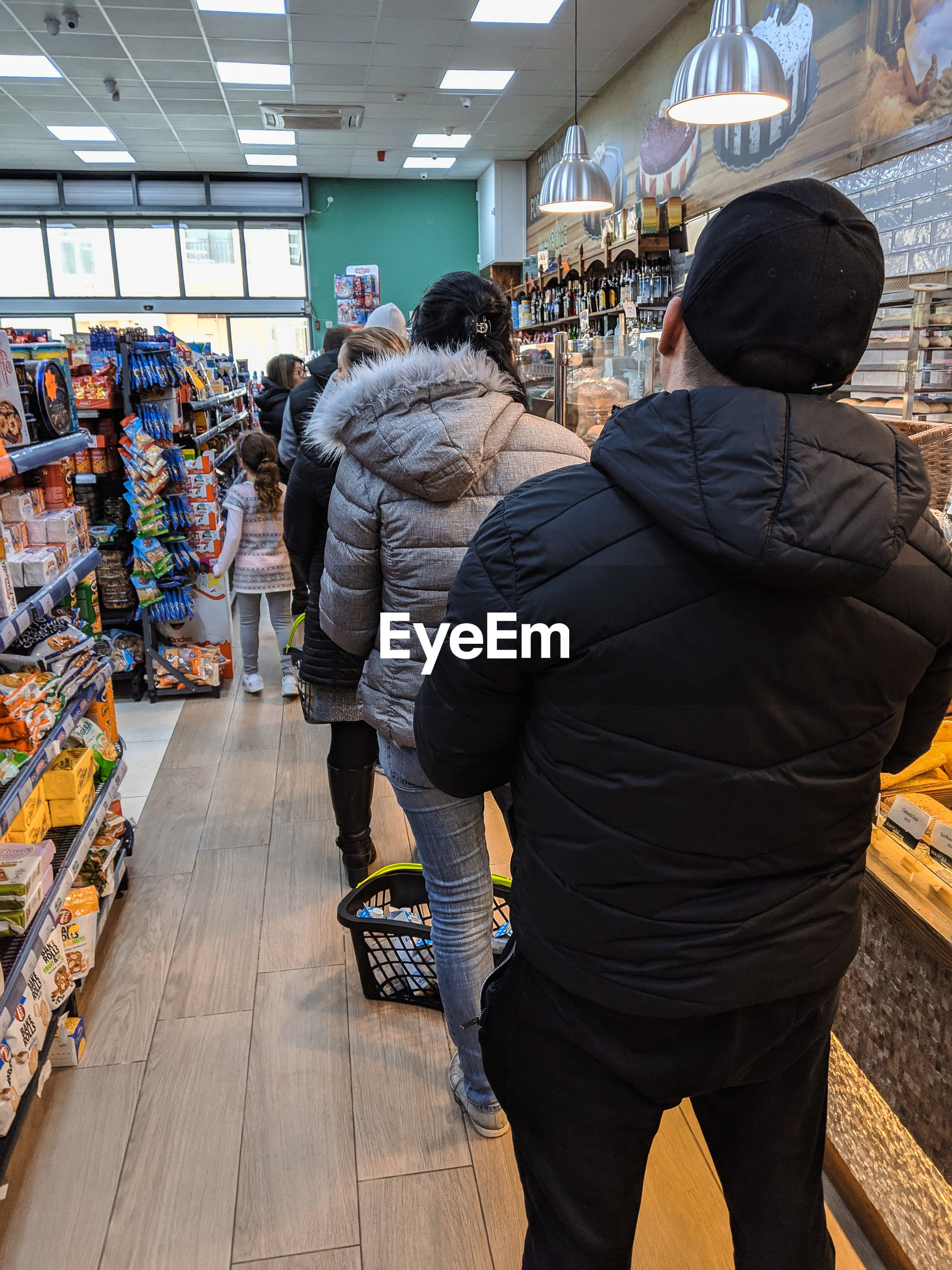 REAR VIEW OF PEOPLE AT STORE IN MARKET