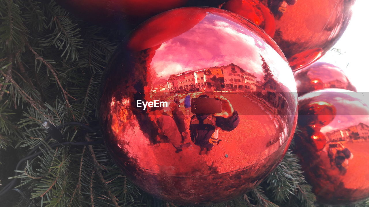 Reflection of people in christmas decoration hanging on tree