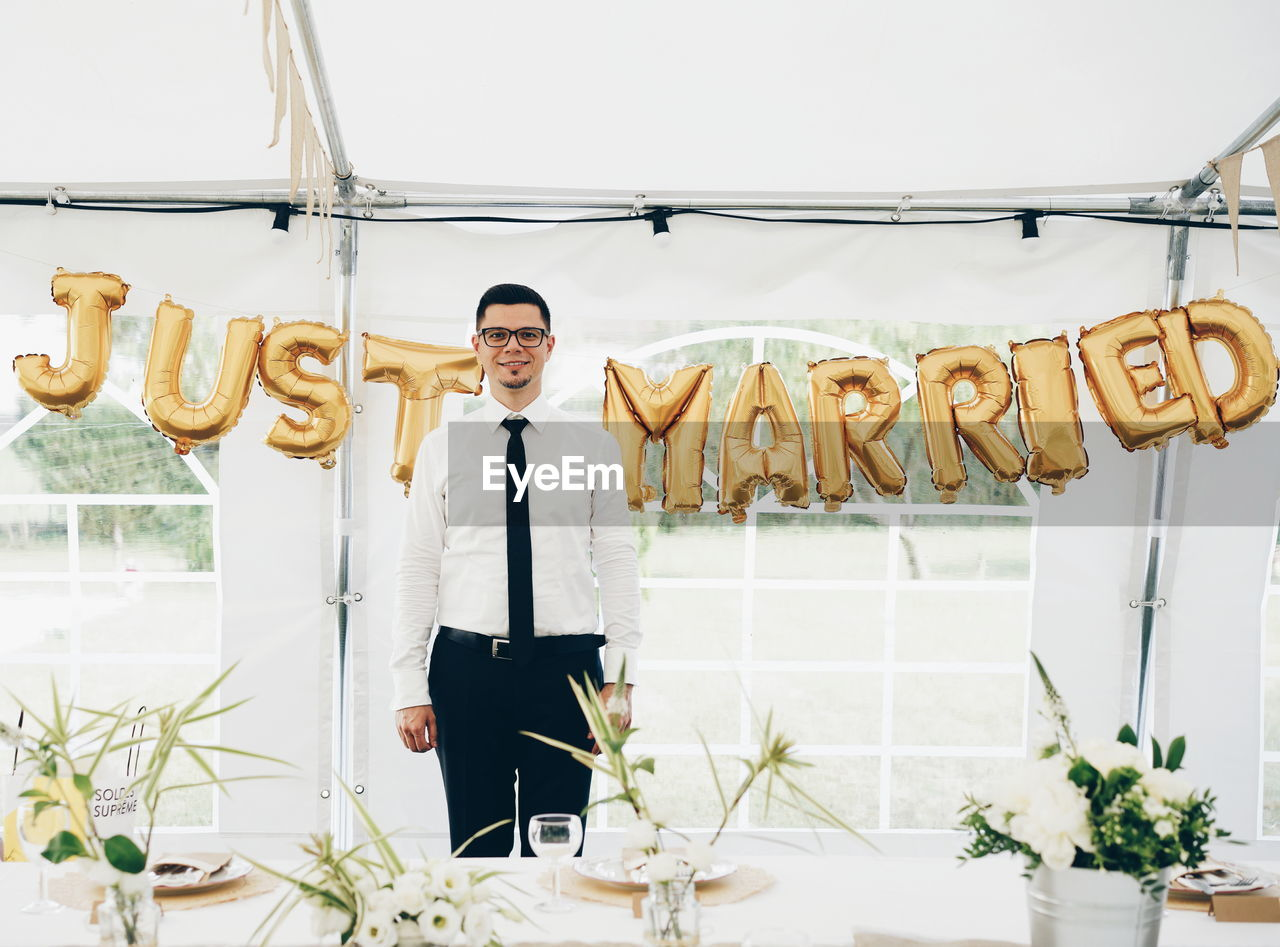 Portrait Of Smiling Bridegroom Standing Against Text In Tent