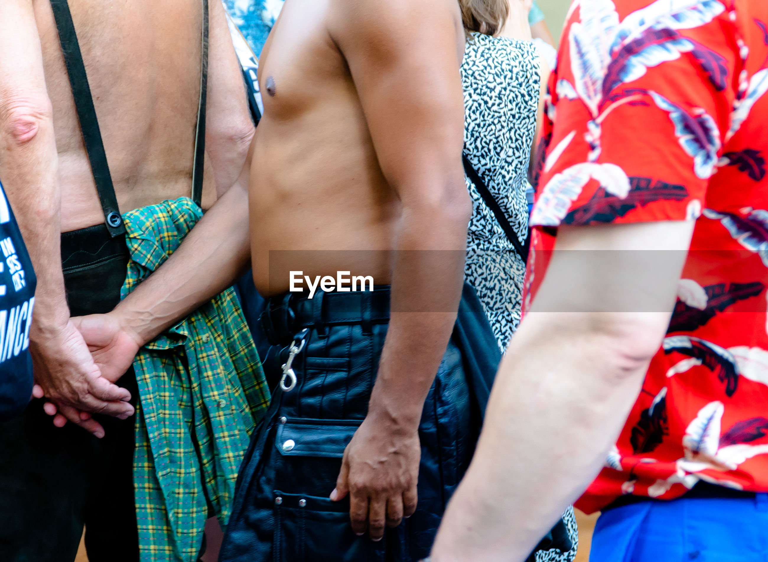 Midsection of gay couple walking in parade