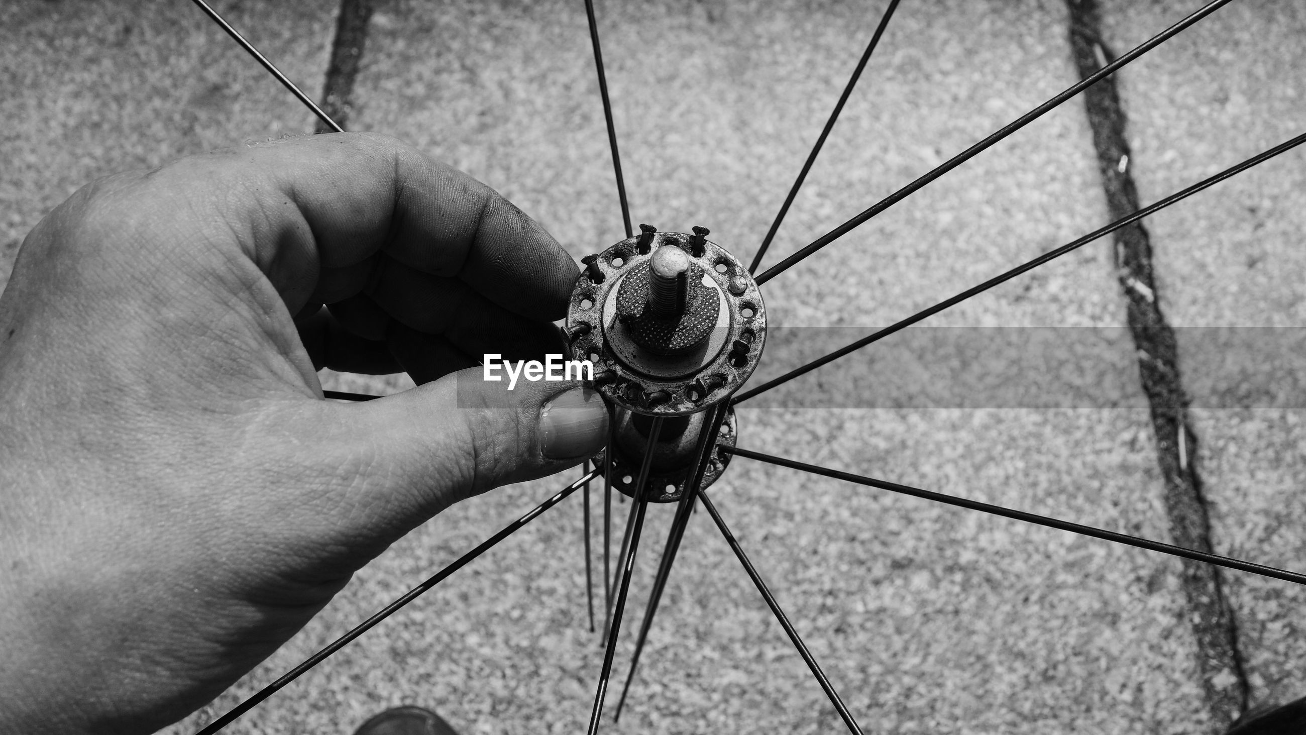Close-up of male hand touching bicycle wheel hub