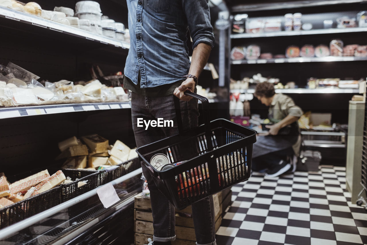 MAN STANDING IN BASKET OF STORE