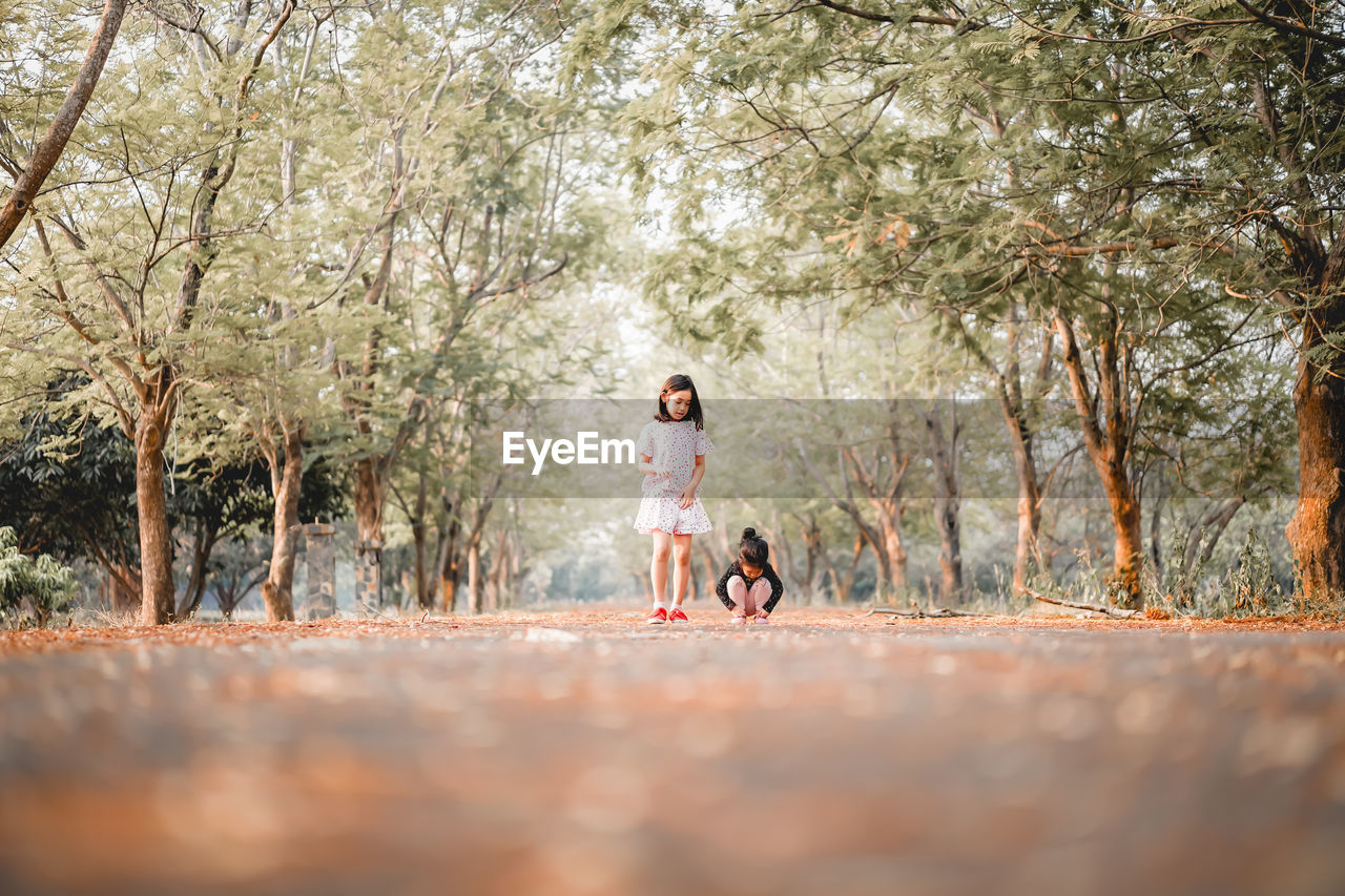 tree, full length, plant, females, real people, women, child, togetherness, casual clothing, nature, childhood, leisure activity, day, two people, pets, walking, front view, outdoors, innocence, daughter
