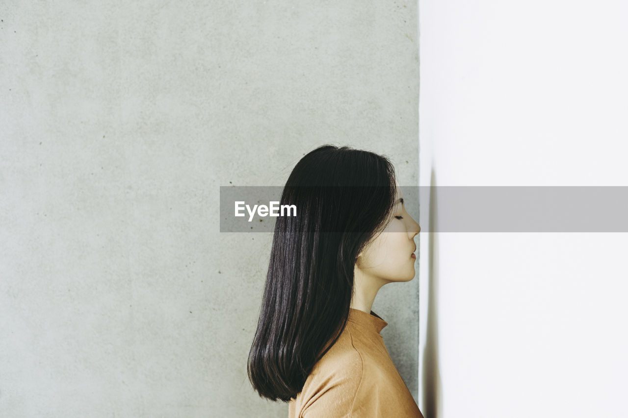 Woman With Eyes Closed Standing By Wall