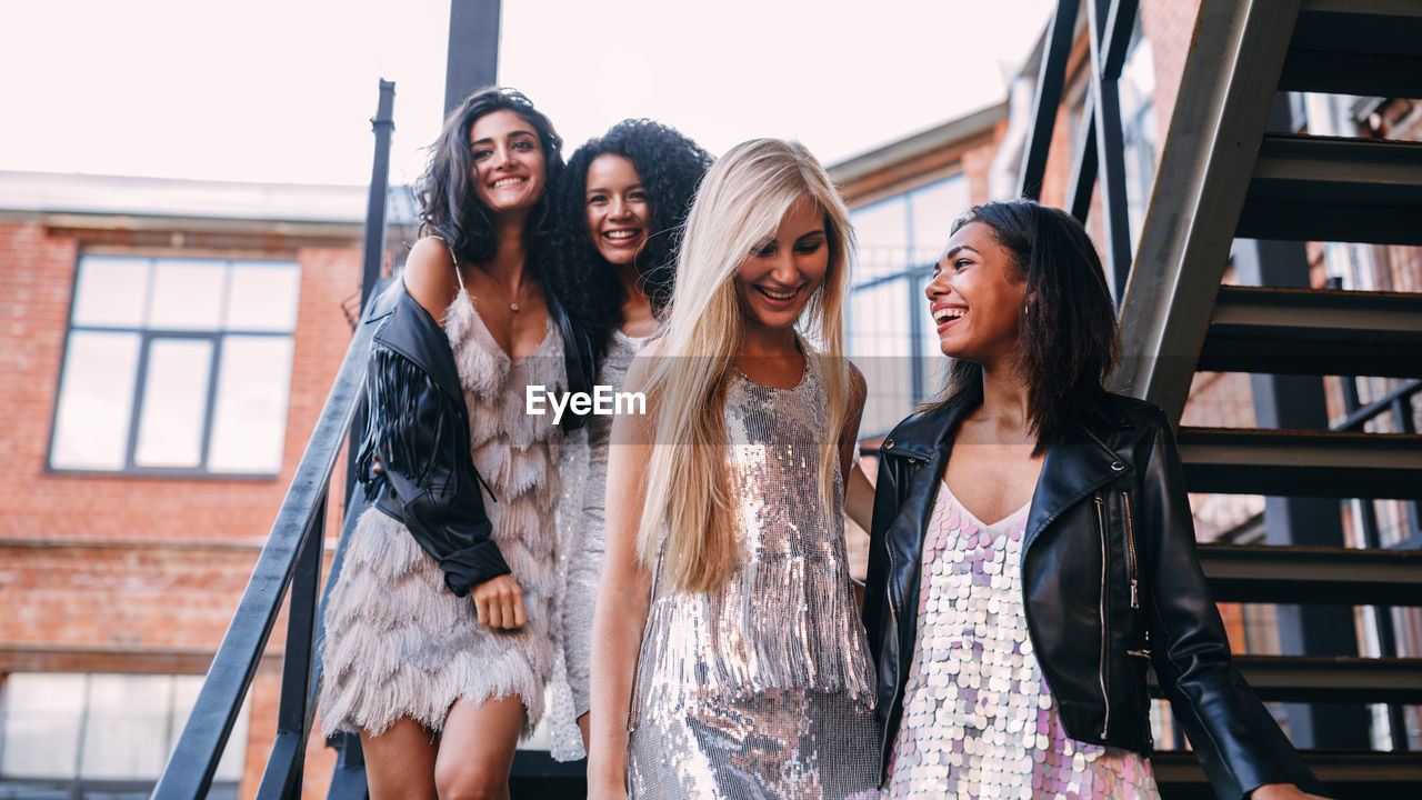 Low angle view of cheerful young female friends moving down on staircase against building